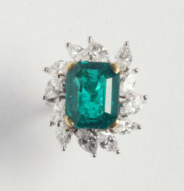 An emerald and diamond cluster ring. Accompanied by report of R.A.G laboratory stating that the emerald  [..]