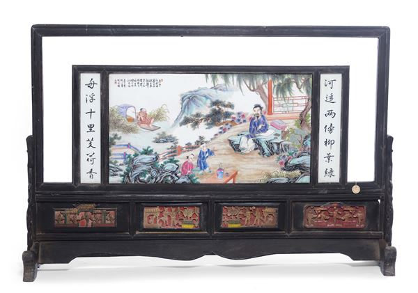 A large porcelain plaque representing figures within a landscape with ideograms on a wooden base, China, Republic, 20th century