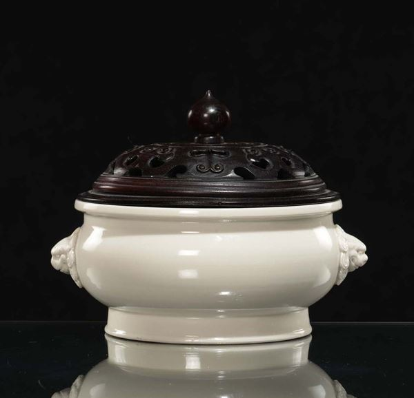 A Blanc de Chine porcelain censer, Dehua, and fretworked wooden cover, China, Qing Dynasty, late 17th  [..]