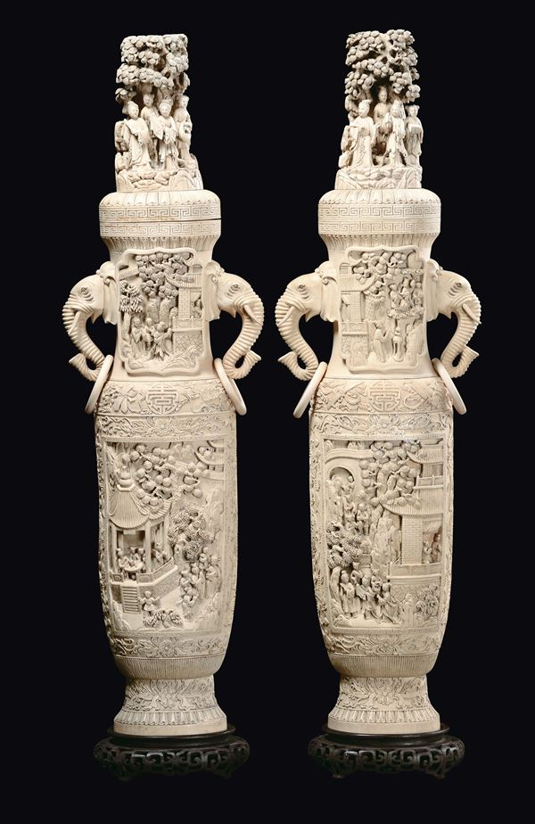 A pair of large ivory vases and cover, elephant heads' double handles, carved with court life scenes,  [..]