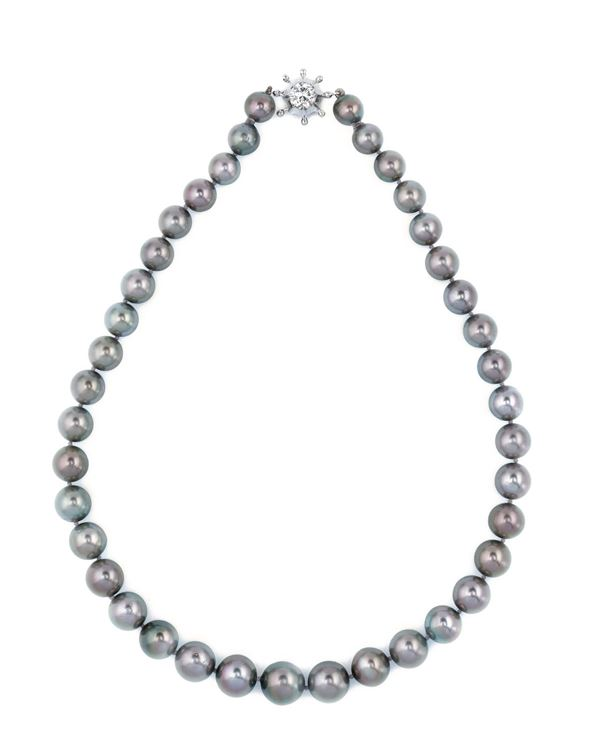 A grey cultured pearl necklace with a diamond clasp