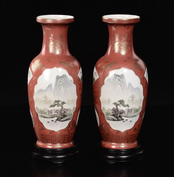 A pair of polychrome enamelled red-ground porcelain vases with a river landscape and trees within reserves, China, 20th century