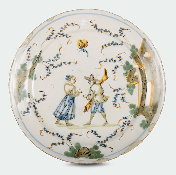 A polychrome majolica plate with two figures and ruins, fortress mark, Ferro Guidobono manufacture, Savona, early 18th century