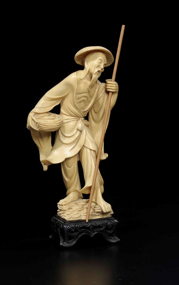 A carved ivory fisher man with stick and basket full of fish, Japan, early 20th century