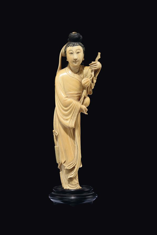A carved ivory figure of black hair Guanyin with peaches, China, early 20th century