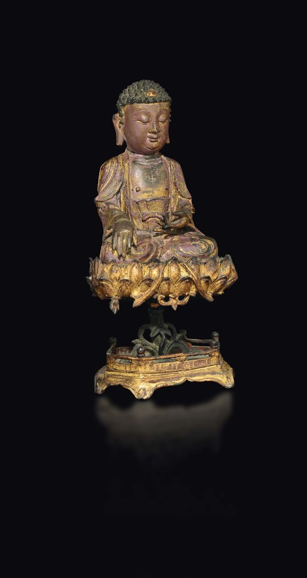 A large semi-gilt bronze figure of Buddha seated on a lotus flower stand, China, Ming Dynasty, 17th century