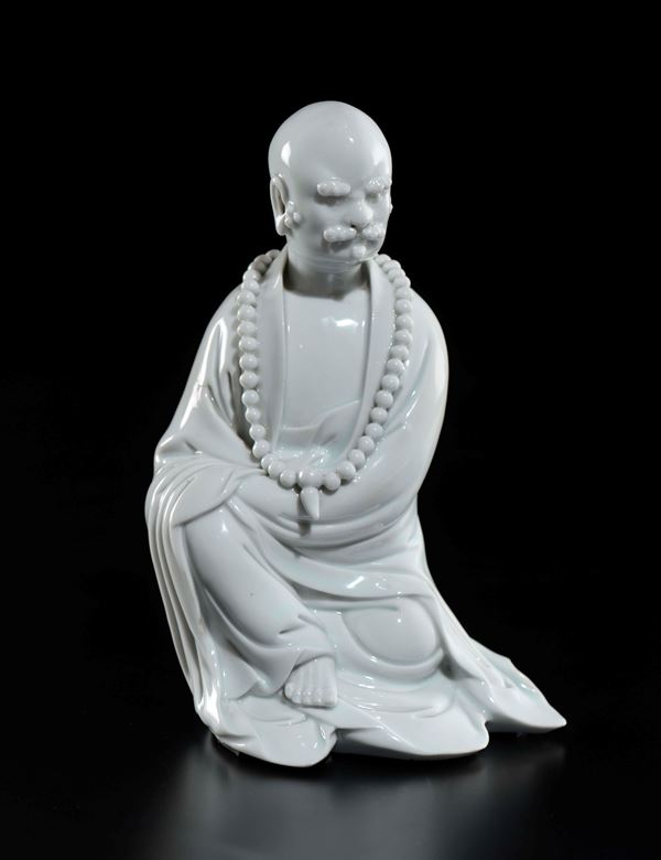 A Blanc de Chine Dehua porcelain dignitary with moustache and necklace beads prayer, China, Qing Dynasty, 18th century