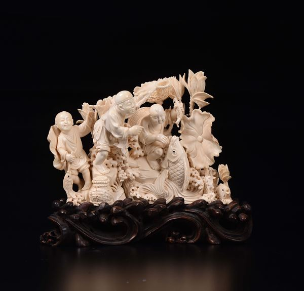 A carved ivory children with fish and flowers group, China, early 20th century