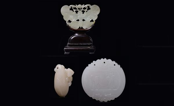 Three carved and fretworked white jades: a small fruit with an animal, a butterfly plaque and a pendant with inscription, China, Qing Dynasty, 19th century