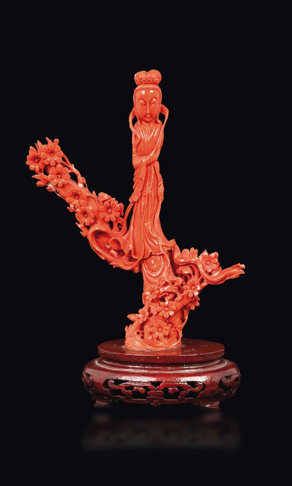 A carved coral figure of Guanyin with flowers, China, early 20th century