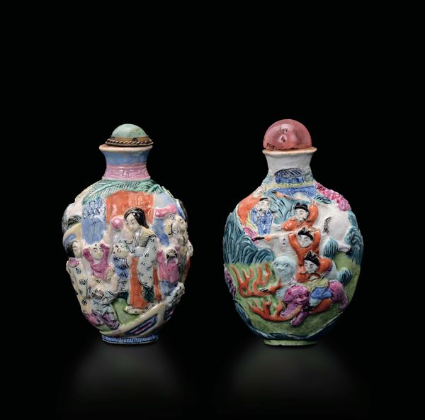 Two polychrome enamelled porcelain snuff bottles with figures in relief, one with children and one with hunting scenes, China, Qing Dynasty, 19th century