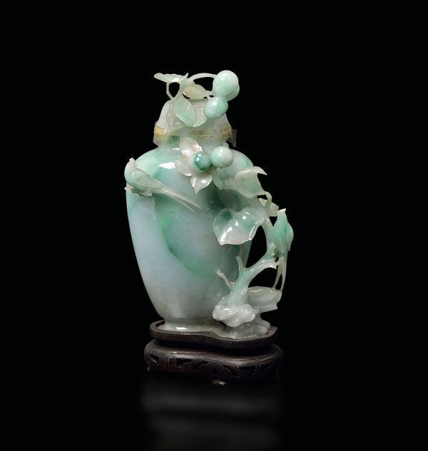 A small apple green shades jadeite vase and cover with peaches and birds in relief, China, early 20th century