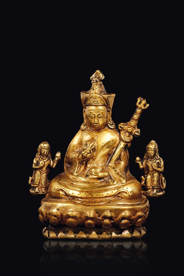 A small gilt bronze figure of seated Lama with vajra and sword, China, Qing Dynasty, 18th century
