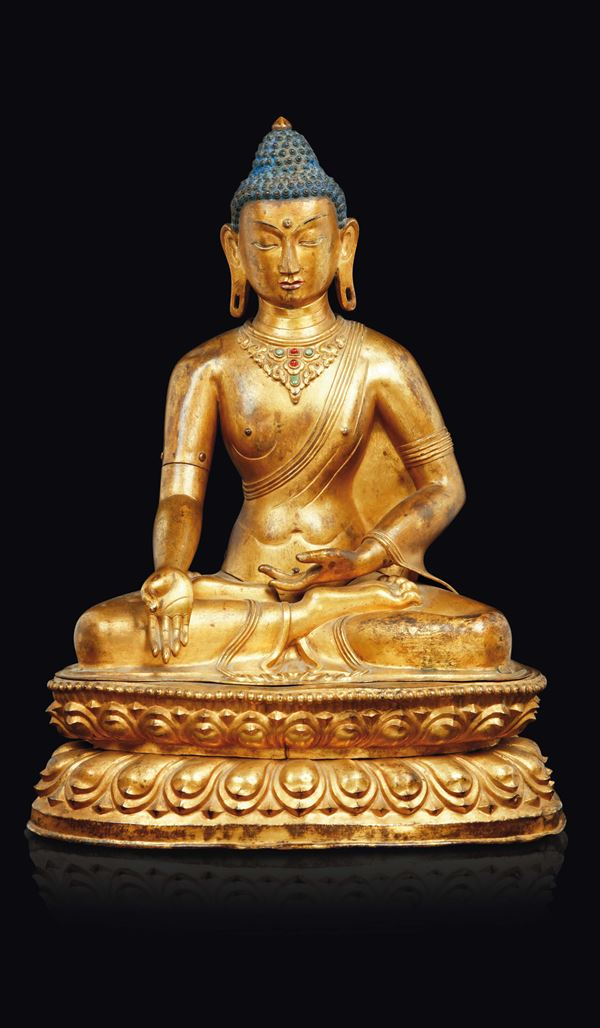 A gilt copper repoussé figure of Buddha seated on a double lotus flower with semi-precious stones inlays and inscription on the back, Tibet, 18th century