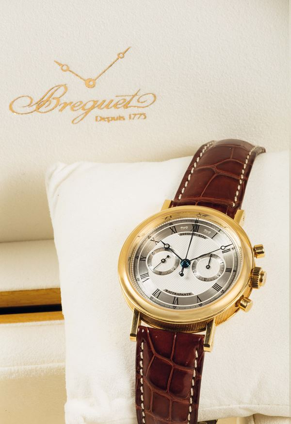 BREGUET, Rattrappante, Ref. 5947. Very fine and rare, 18K yellow gold wristwatch with round and oval button split-seconds chronograph, register and an 18K yellow gold Breguet deployant clasp. Accompanied by the original box, papers and Guarantee. Made in 2005.