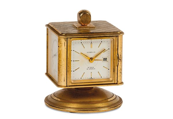 GUBELIN, No. 5044. Fine, revolving gilt-brass desk compendium with 8-day going clock, date, hygrometer, barometer and thermometer. Made circa 1960
