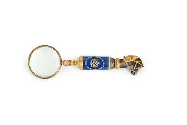 A magnifying glass in molten, chiselled and gilded silver, precious stones and enamel. Stamps for Fabergé  [..]