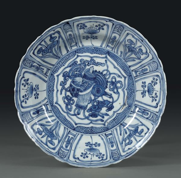 A porcelain plate with a white and blue decoration. The brim is divided into quarters. China, Qing dynasty, 18th century