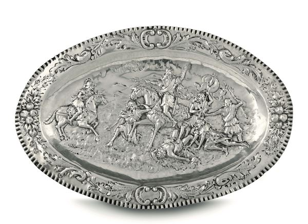 An oval parade platter in embossed and chiselled silver, 19-20th century manufacture