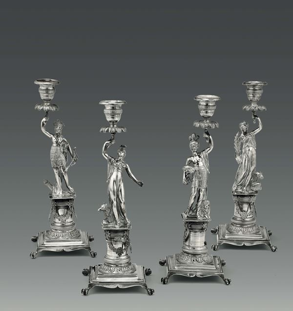 A group of four candlesticks depicting the four continents in molten, embossed and chiselled silver,  [..]
