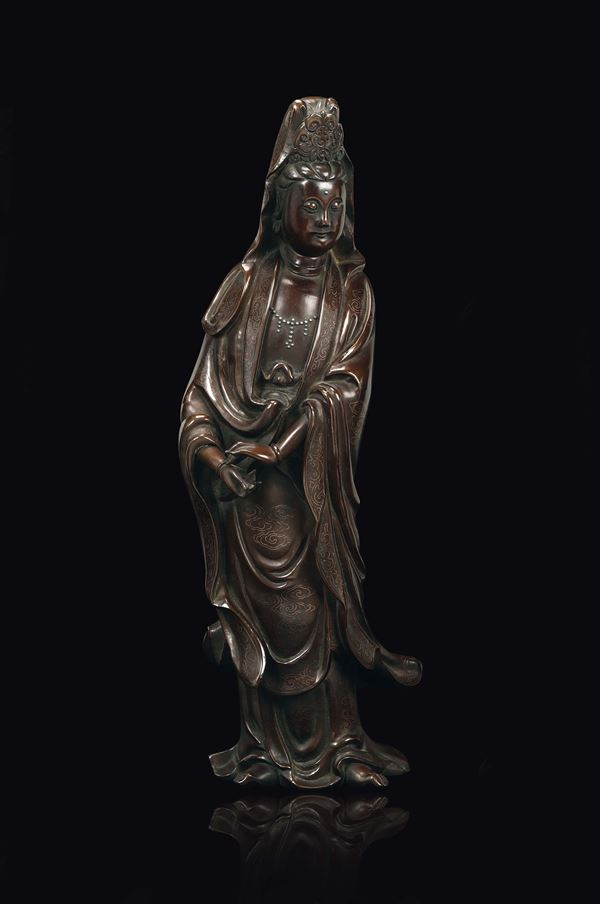 A bronze figure of standing Guanyin with silver inlays with clouds decoration, China, Qing Dynasty,  [..]