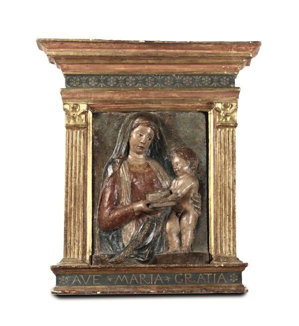 A Madonna with child, a relief in polychrome terracotta within a ciborium frame in painted and gilded wood, Renaissance modeller active in Veneto in the second half of the 15th century