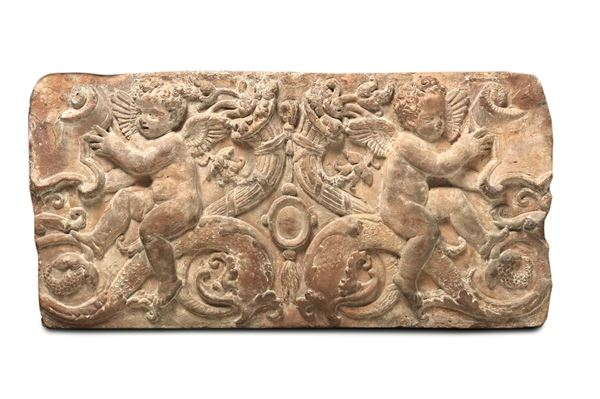 A Renaissance decoration in terracotta depicting puttos with dolphins and cornucopias, Tuscan modeller from the 15th century