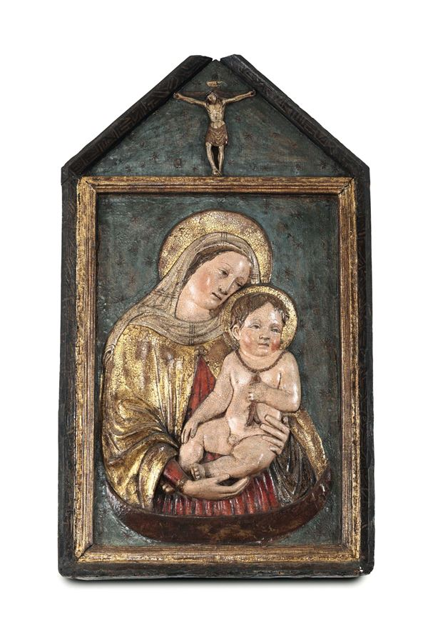 A relief in terracotta, painted and gilded, depicting a Madonna with Child. Master of the Polyptych  [..]