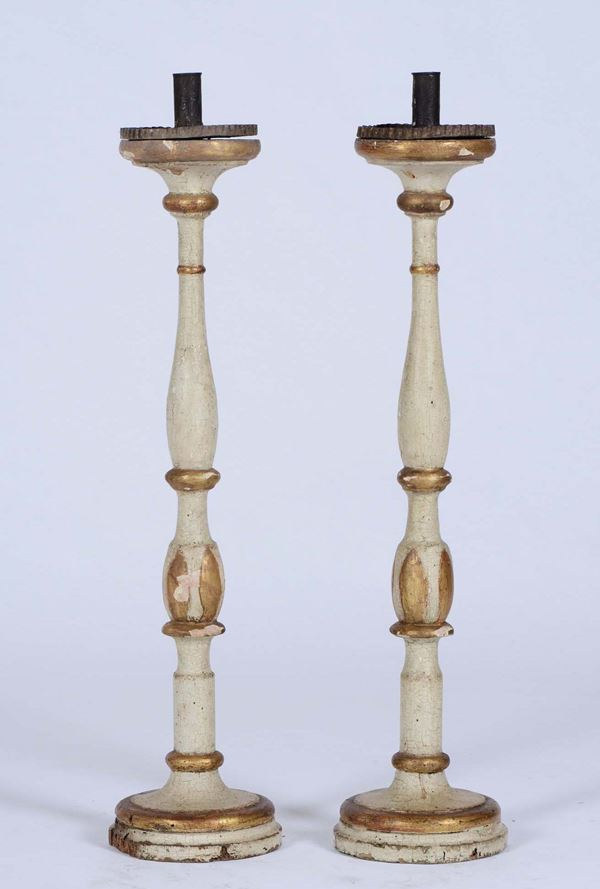 A pair of turned, lacquered and gilt wood candle holders, 18th-19th century