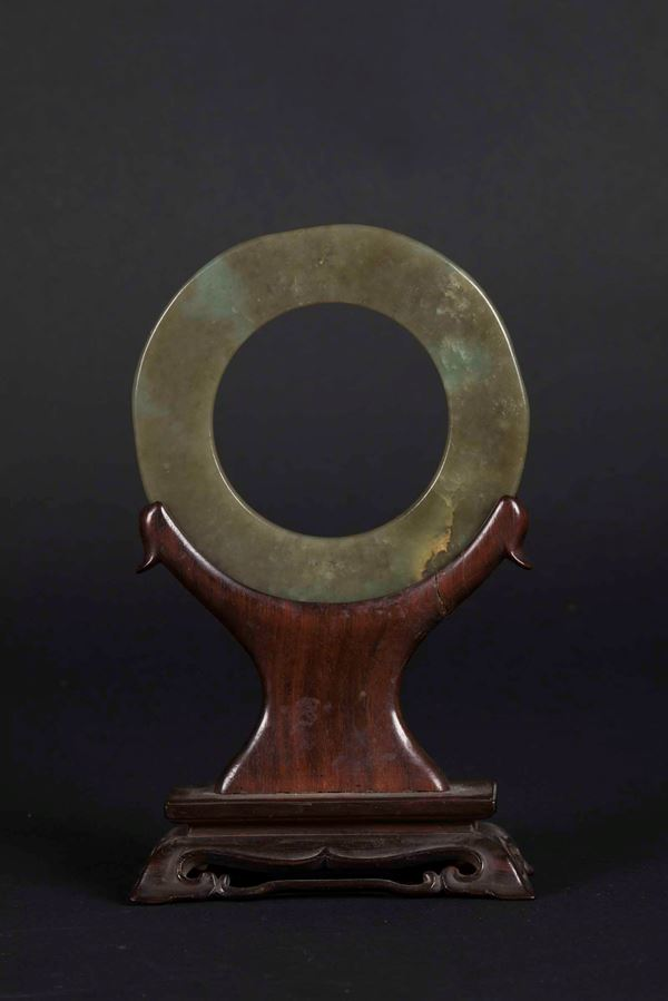 A Bi disk in green jade and russet on a wooden base, China, Qing dynasty, 19th century