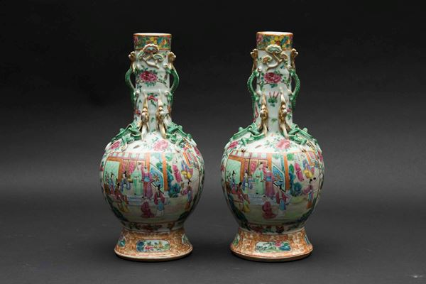 A pair of Canton porcelain vases with polychrome enamels depicting everyday life scenes and embossed  [..]