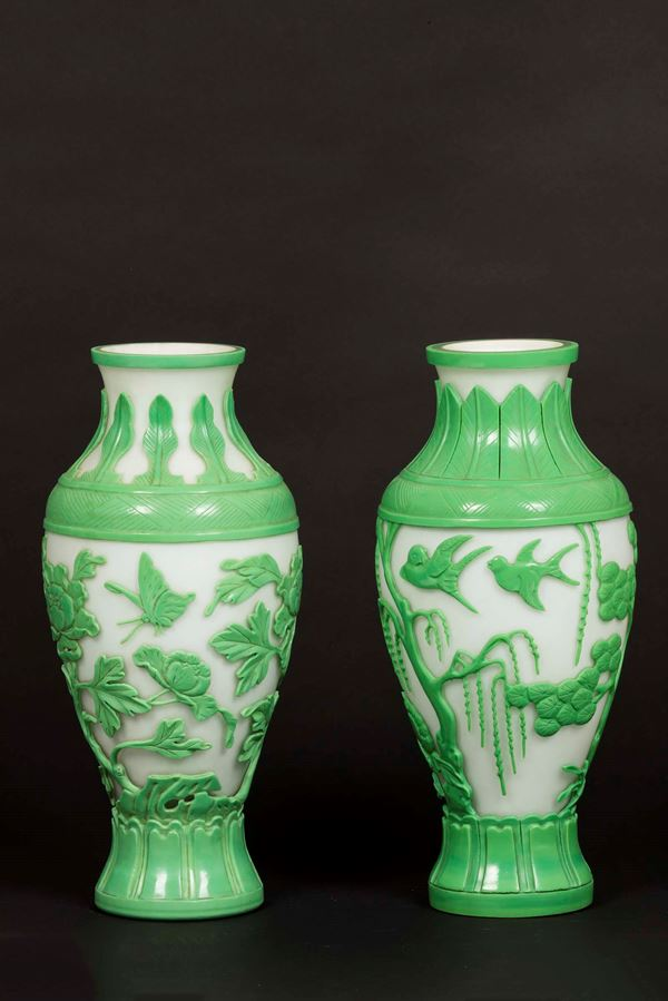 A pair of vases in Beijing glass with a green botanical decor on a white backdrop, China, 20th century