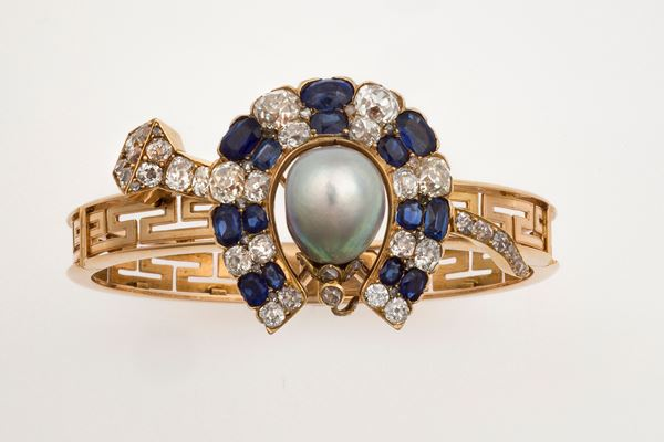 Bangle in gold with removable horse shoe decoration set with diamonds and sapphires and a natural pearl